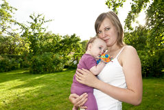 Young mother in the garden with a baby Royalty Free Stock Photos