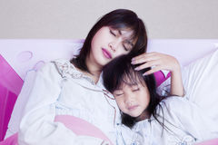 Young mother and girl sleeping on bed Royalty Free Stock Photo