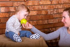 Young mother gives his son an green apple to eat. On a red bricks wall  background. One year baby in jeans sitting. Young mother gives his son an green apple to stock photo
