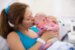 Young mother giving birth to a baby. Mother giving birth to a baby. Newborn baby in delivery room. Mom holding her new born child after labor. Female pregnant stock image