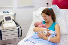 Young mother giving birth to a baby. Mother giving birth to a baby. Newborn baby in delivery room. Mom holding her new born child after labor. Female pregnant royalty free stock images