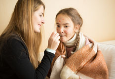 Young mother giving medicines on spoon to daughter caught flu Stock Photos