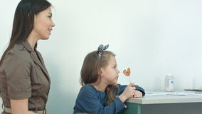 Young mother giving money to a doctor for her daughter visit stock footage