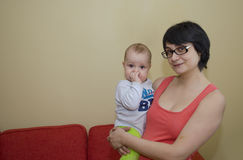 Young mother with glasses holds a small child in her arms Royalty Free Stock Photography