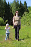 Young mother go with little daughter near green forest at summer Royalty Free Stock Photos