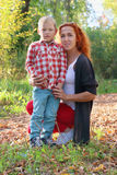 Young mother and handsome little son in autumn park. At sunny day Royalty Free Stock Images