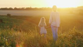 A young mother is having a fun weekend with her little daughter, walking together to meet the sunset sun.  stock footage