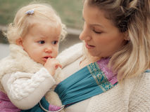 Young mother having her little daughter in baby carrier scarf. Portrait of a mother carrying her little baby in a baby carrier scurf in the park Stock Photo