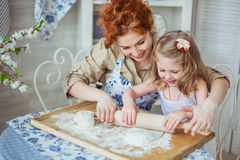 Young mother help to roll a dough to her daughter. Portrait of A young mother help to roll a dough to her little daughter  on a kitchen Royalty Free Stock Photos