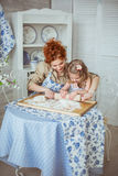 Young mother help to roll a dough to her little daughter. A young mother help to roll a dough to her little daughter  on a kitchen Stock Image