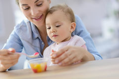 Young mother helping eating to her baby Royalty Free Stock Image