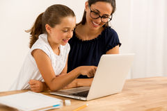 Helping with homework. Young mother helping her daughter with homework at home stock image