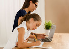 Helping with homework. Young mother helping her daughter with homework at home stock photography