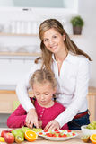 Young mother helping her daughter in the kitchen Stock Photography