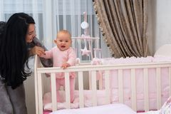 Young mother helping her little daughter stand. royalty free stock photo