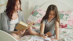 Young mother helps her little cute daughter with homework for elementary school. Loving mom reading a book and girl