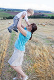 Young mother and her little son having fun in straw field Stock Photos