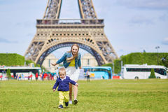 Young mother and her adorable toddler son. Beautiful young mother and her adorable toddler son having fun together near the Eiffel tower in Paris, boy is running royalty free stock photo