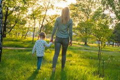 Young mother with her amusing daughter are walking through park Stock Photo