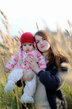 Young mother and her baby. Young mother is holding her little baby walking in a meadow Royalty Free Stock Images