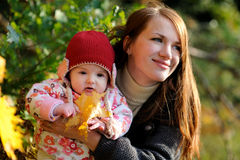Young mother and her baby. Young mother is holding her little baby and smiling Royalty Free Stock Image