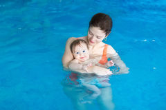 Young mother and her baby in baby swimming lesson. Young mother and her baby enjoying a baby swimming lesson in the swimming pool stock image