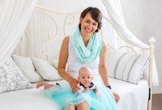 Young mother with a her baby on the bed. In the room Stock Images