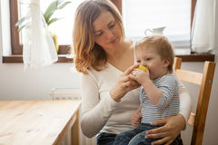 Young mother and her baby boy eating an apple Stock Photos