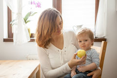 Young mother and her baby boy eating an apple Royalty Free Stock Photo