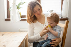 Young mother and her baby boy eating an apple Royalty Free Stock Image