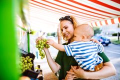 Young mother with her baby boy at outdoor market. Stock Photos