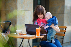 Young mother with her baby boy working in cafe Royalty Free Stock Photo