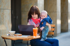Young mother with her baby boy working in cafe Stock Photo