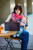 Young mother with her baby boy working in cafe stock image