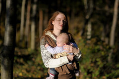 Young mother with her baby in a carrier. Young mother with her little baby in a carrier Stock Photography