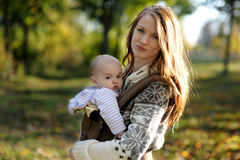 Young mother with her baby in a carrier. Young mother with her little baby in a carrier Royalty Free Stock Images