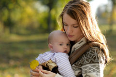 Young mother with her baby in a carrier. Young mother with her little baby in a carrier Royalty Free Stock Image