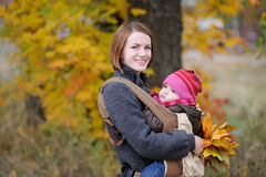 Young mother and her baby in a carrier Stock Images