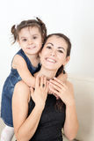Young mother with her baby. On the couch Stock Photos