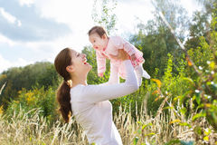 Young mother with her baby daughter in sunny Stock Image