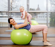 Young mother and her baby doing yoga exercises on rugs at fitness studio. Royalty Free Stock Photos
