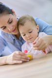 Young mother with her baby eating Stock Photography