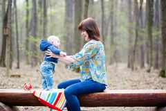 Young mother with her baby in a forest Stock Photo