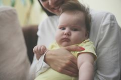Young mother with her baby girl at home. Close up. stock photo