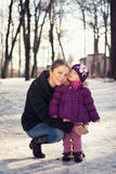 Young mother and her baby girl outdoors on a snowy winter day Royalty Free Stock Image