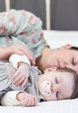 Young mother and her baby girl sleeping in the bed Stock Image