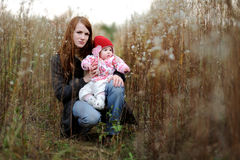 Young mother and her baby in a meadow. Young mother and her little baby in a meadow Royalty Free Stock Photos