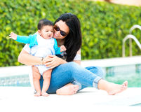 Young mother with her baby near the swimming pool. Beautiful young mother playing with baby boy near the swimming pool on a sunny day stock image