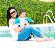 Young mother with her baby near the swimming pool. Beautiful mother playing with baby boy near the swimming pool on a sunny summer day stock photography