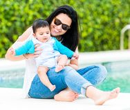 Young mother with her baby near the swimming pool. Beautiful young mother playing with baby near the swimming pool on a sunny summer day royalty free stock photo
